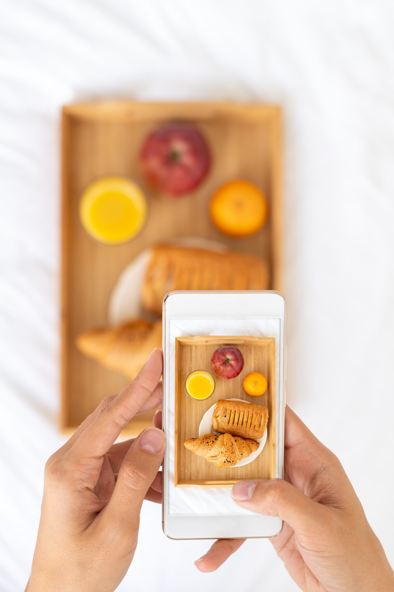 Blogger taking photos of food, shooting Breakfast in bed at hotel on mobile phone, tray with juice